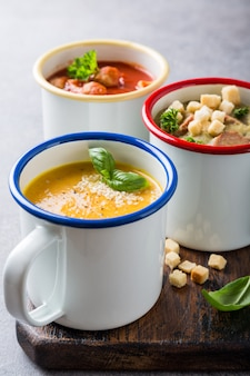 Assortiment de délicieuses soupes faites maison dans des tasses en émail avec des ingrédients. concept de nourriture saine