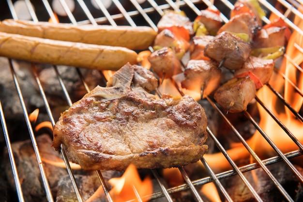 Assortiment de délicieuses viandes grillées sur les charbons sur un barbecue.
