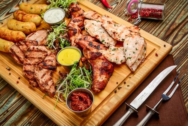 Assortiment de délicieuses viandes et légumes grillés avec salade fraîche et sauce bbq sur une planche à découper sur fond en bois. grand ensemble de plats de viande chaude