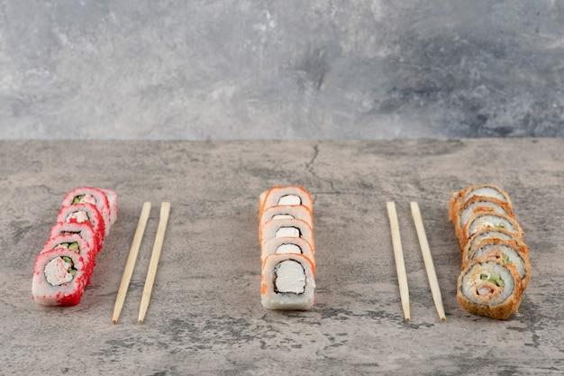 Assortiment de délicieux rouleaux de sushi placés sur fond de marbre