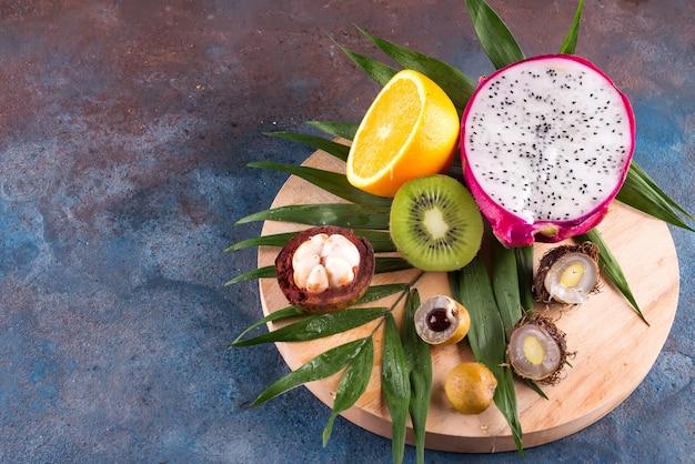 Assortiment de demi-fruits tropicaux sur un rond en bois joue sur un motif de fond en pierre.