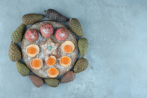 Assortiment de desserts au milieu d'un cercle de pomme de pin sur marbre.
