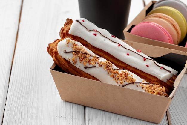 Assortiment de desserts dans des boîtes sur fond de bois blanc
