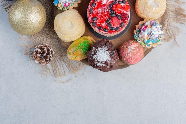 Un assortiment de desserts sur une planche en bois ornée de babiole et pomme de pin sur une surface en marbre