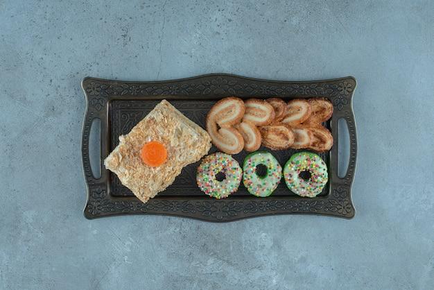 Assortiment de desserts avec une tranche de gâteau, beignet et biscuits feuilletés sur un plateau orné sur une surface en marbre