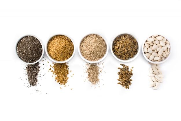 Assortiment de différentes graines dans un bol isolé sur fond blanc graines de citrouille, lin, chia, tournesol et sésame