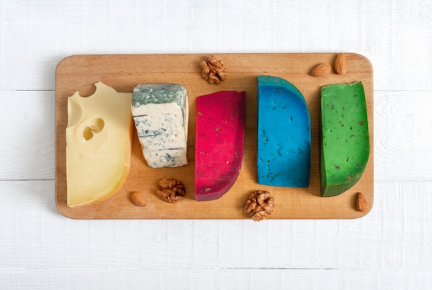 Assortiment de différentes sortes de fromages artisanaux. plateau de fromages sur une table en bois blanche. vue de dessus.
