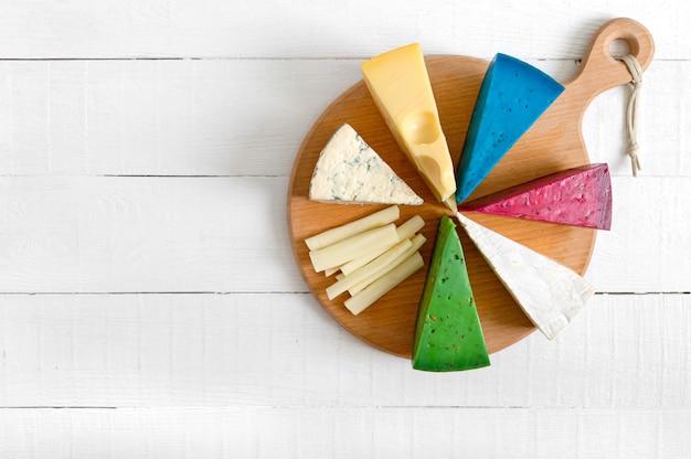 Assortiment de différentes sortes de fromages artisanaux. plateau de fromages sur une table en bois blanche