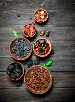 Assortiment de différentes sortes de fruits secs dans des bols. sur un fond en bois.