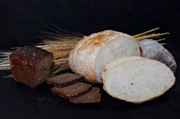 Assortiment de différentes sortes de pain blanc et noir sur fond noir.