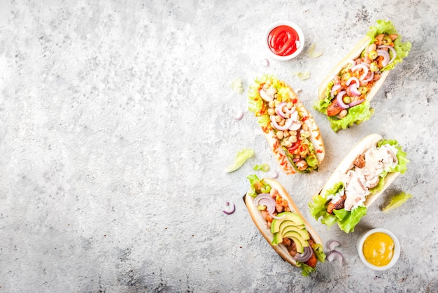 Assortiment de différents hot-dogs végétaliens faits maison aux carottes, avec oignon frit, avocat, piment, champignons, tomates et haricots, fond en pierre grise vue de dessus