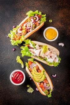 Assortiment de différents hot-dogs végétaliens faits maison aux carottes, avec oignon frit, avocat, piment, champignons, tomates et haricots, fond rouillé foncé vue de dessus