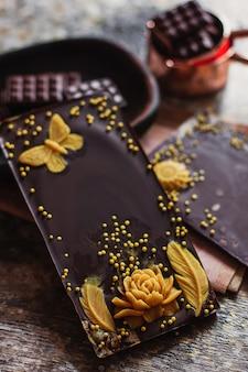 Assortiment de différents types de chocolat créatif dans une assiette en bois sculptée, avec des accessoires vintage sur la surface