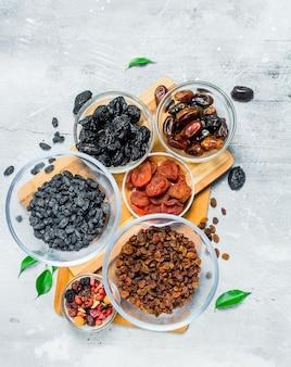 Assortiment de différents types de fruits secs dans des bols. sur un fond rustique.