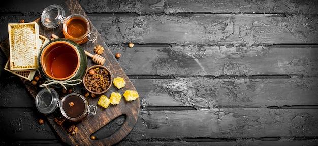Assortiment de différents types de miel. sur fond rustique noir.