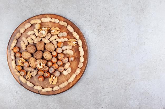 Un assortiment de différents types de noix sur planche de bois sur fond de marbre. photo de haute qualité