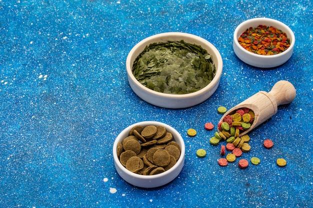 Assortiment de différents types de nourriture pour les poissons d'aquarium. flocons, spiruline, pilules, mélange. fond de mer bleu marine