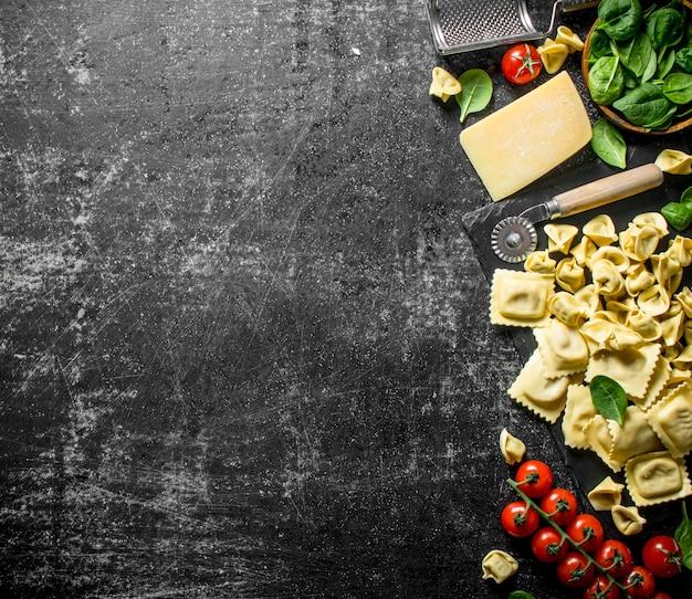 Un assortiment de différents types de pâtes crues avec du fromage, des tomates et des herbes sur table rustique