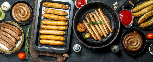 Assortiment de différents types de saucisses frites sur table rustique noire.