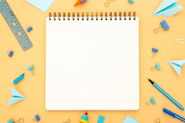 Assortiment d'éléments de bureau avec cahier vide