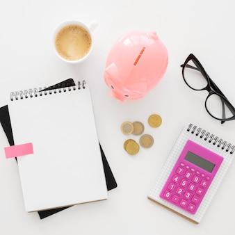 Assortiment d'éléments financiers vue de dessus avec bloc-notes vide