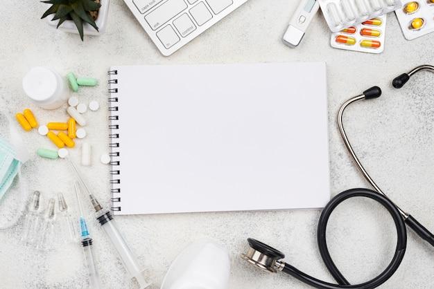 Assortiment d'éléments médicaux à plat avec bloc-notes vide
