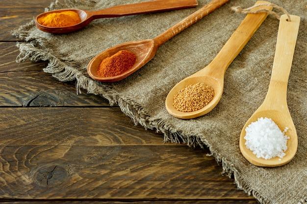 Assortiment d'épices dans des cuillères en bois sur une toile de jute sur fond de bois.