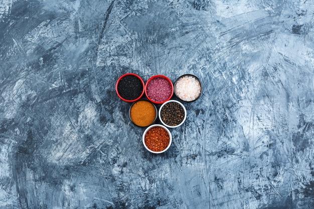 Assortiment d'épices dans de petits bols vue de dessus sur un fond de plâtre gris