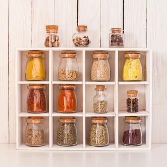 Assortiment d'épices sèches dans des bouteilles en verre vintage dans une boîte en bois