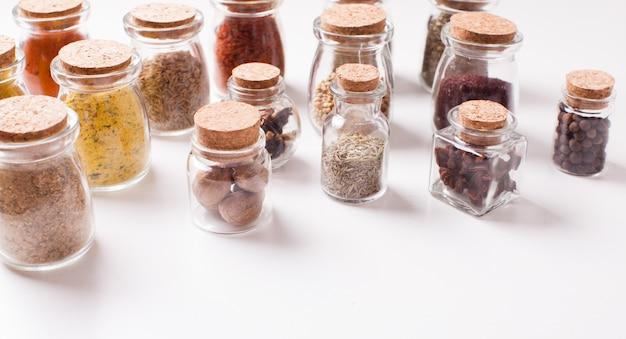 Assortiment d'épices sèches dans des bouteilles en verre vintage sur fond blanc