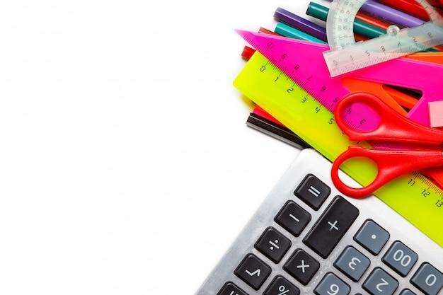 Assortiment de fournitures scolaires, y compris des stylos, des crayons, des ciseaux, de la colle et une règle, sur fond blanc