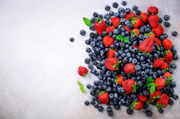 Assortiment de fraises, myrtilles, cassis, feuilles de menthe. cadre de nourriture, conception de la frontière. concept végétalien et végétarien. fond de baies d'été