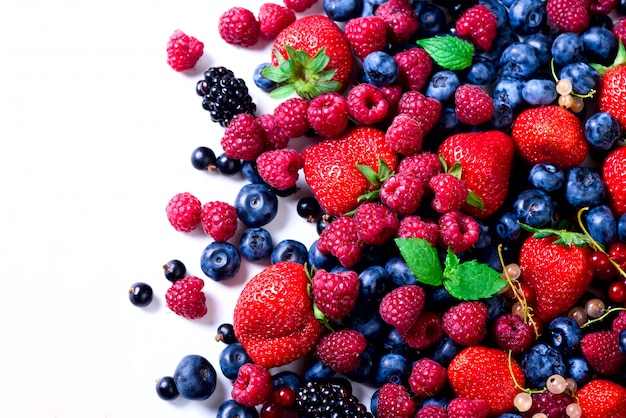 Assortiment de fraises, myrtilles, cassis, feuilles de menthe. cadre de nourriture, conception de la frontière. concept végétalien et végétarien.