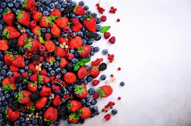 Assortiment de fraises, myrtilles, cassis, feuilles de menthe. fond de baies d'été. cadre alimentaire et conception de la bordure. vegan, concept végétarien.