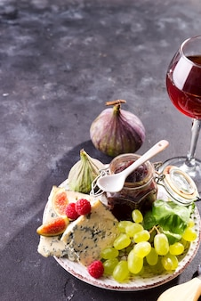 Assortiment de fromage, de baies et de raisins avec du vin rouge dans des verres sur la surface de la pierre