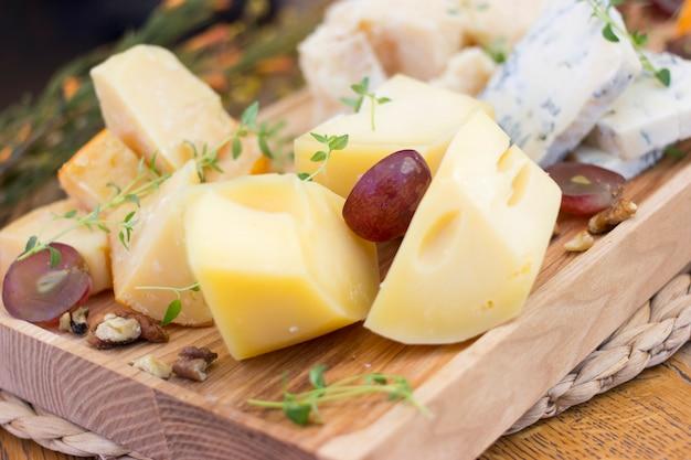 Assortiment de fromages avec baies, noix et légumes verts sur un plateau en bois