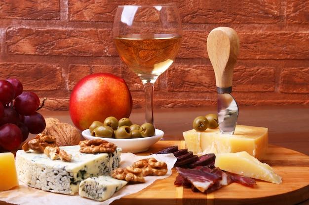 Assortiment de fromages avec fruits, raisins, noix et couteau à fromage sur un plateau en bois.