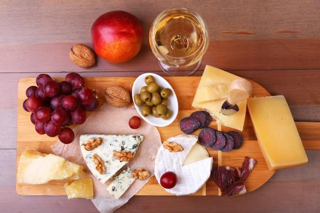 Assortiment de fromages, noix, raisins, fruits, viande fumée et un verre de vin sur une table de service