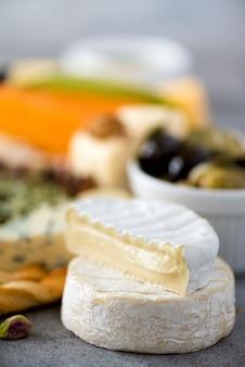Assortiment de fromages à pâte dure, semi-molle et molle avec des olives, des bâtons de pain grissini, des câpres, du raisin. assiette d'apéritif sélection fromages.