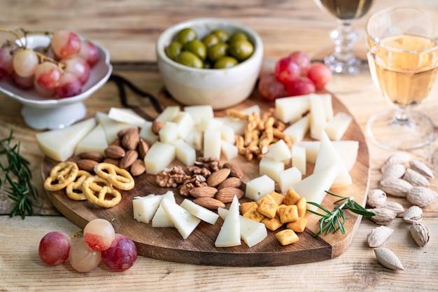 Assortiment de fromages sur une planche à découper en bois en forme de coeur. fromage, raisins, noix, olives, romarin et un verre de vin blanc.