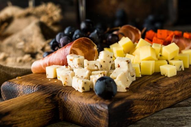 Assortiment de fromages sur plaque de planche de bois.