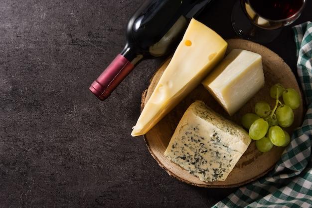 Assortiment de fromages et de vin sur fond noir.