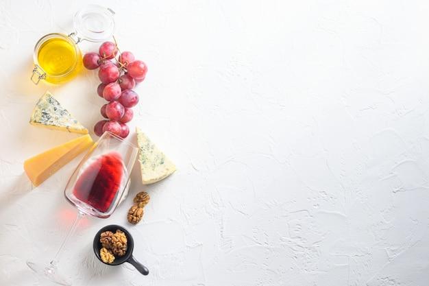Assortiment de fromages et de vin rouge sur fond texturé blanc.