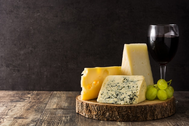 Assortiment de fromages et de vin sur une table en bois.
