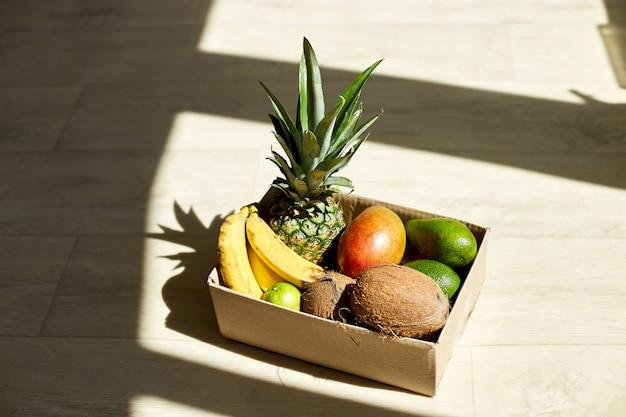 Assortiment de fruits exotiques biologiques en boîte, soleil.