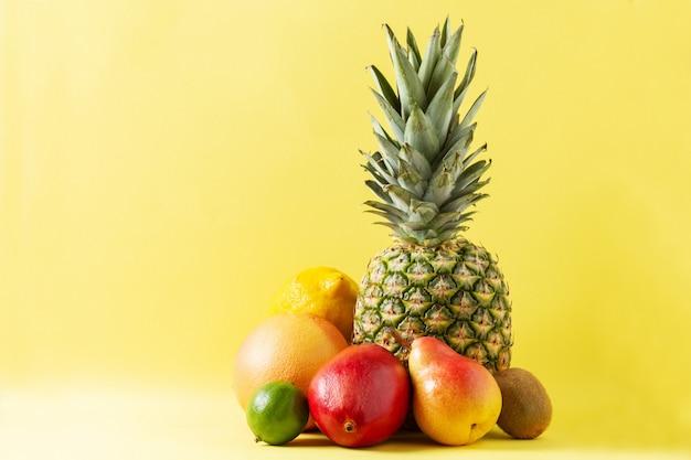 Assortiment de fruits tropicaux sur fond jaune ananas, pamplemousse, poire, mangue, citron vert, citron et kiwi