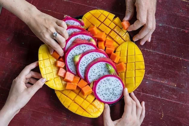 Assortiment de fruits tropicaux et mains de personnes, gros plan. délicieux dessert.