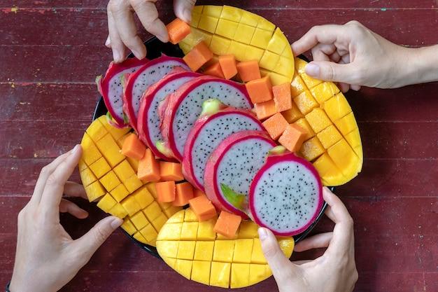 Assortiment de fruits tropicaux et mains de personnes, gros plan. dessert délicieux. groupe d'amis heureux ayant de la bonne nourriture, profitant de la fête et de la communication. mangue, papaye, pitahaya et mains, vue de dessus