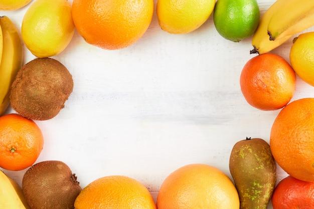 Assortiment de fruits tropicaux orange, mandarine, banane, pamplemousse, citron, citron vert, kiwi. ensemble de fruits frais. vue de dessus, espace copie.