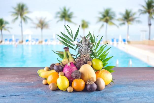 Assortiment de fruits tropicaux sur la plage: orange, ananas, citron vert, mangue, fruit du dragon, orange, banane, ramboutan et lichi